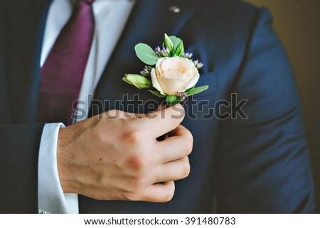 White freesia wedding boutonniere on suit of groom. - stock photo