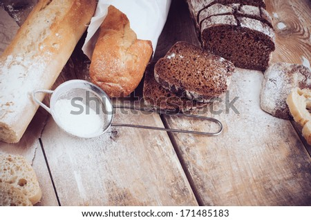 White french baguette and fresh rustic loaf of wholemeal rye bread, sliced �¢??�¢??and flour on a wooden board, bakers, food background is. - stock photo