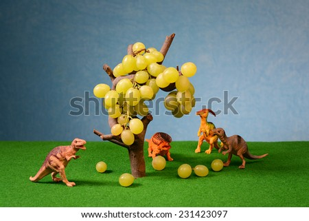 White fresh grapes and animal figures on the table - stock photo