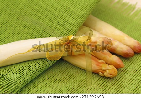 White fresh peeled asparagus with green and yellow bow on a background of four asparagus and green natural burlap fabric texture  background - stock photo