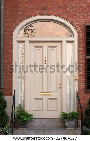 White Front Door with Surrounding White Arch with Lunette and Potted Plants - stock photo