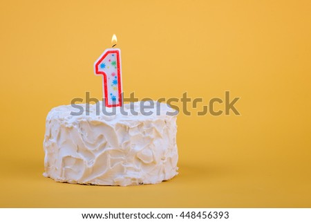 White frosted cake with candle 1 lit on top of it. - stock photo