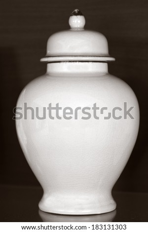 White funeral urn jar shape complete view isolated on dark wooden background.Philosophical concept photo of life ,death, cremation, reincarnation, spiritual , religious , soul ,spirit and spirality - stock photo