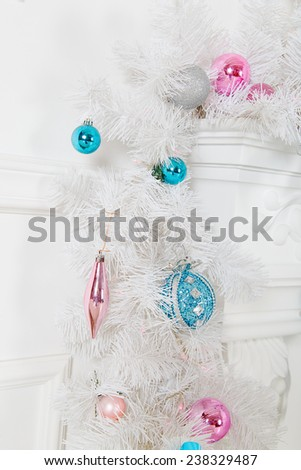 White garland above the fireplace with blue skates and toys - stock photo