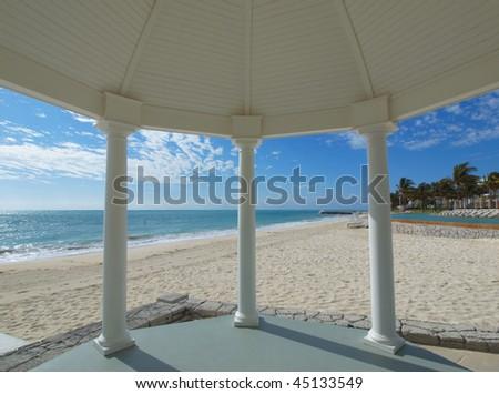 White gazebo for weddings overlooking tropical beach - stock photo