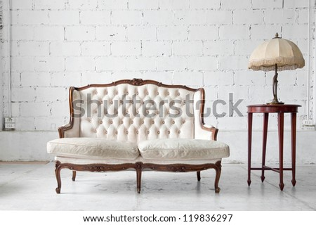 White genuine leather classical style sofa in vintage room with desk lamp - stock photo