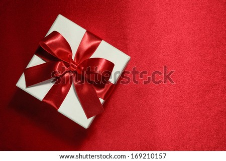White gift box on red background - stock photo