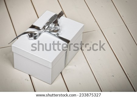 White gift box with silver ribbon bow on wooden floor background - stock photo