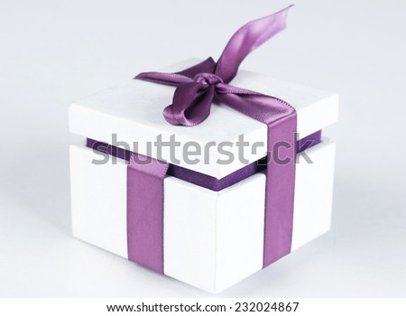 White gift box with violet ribbon bow, isolated on white background - stock photo