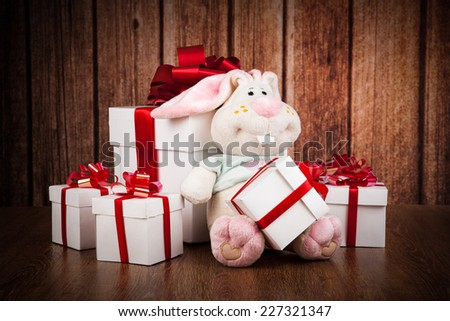 white gift boxes and soft toy on a wood background - stock photo