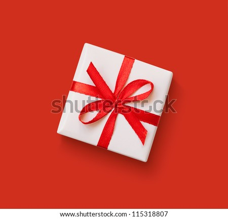 White gift with red ribbon on red background - stock photo