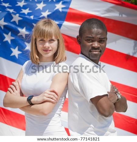 White girl and black guy outdoors. White girl and black guy against American flag - stock photo