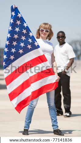 White girl and black guy outdoors. Young man and woman with american flag - stock photo
