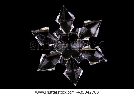 white glass snowflake isolated on the black background - stock photo