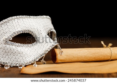 White glittering mask with old paper scroll and paper on wooden table - stock photo