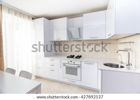 White glossy modern kitchen with stone counter and built-in household appliances in bright colors interior - stock photo