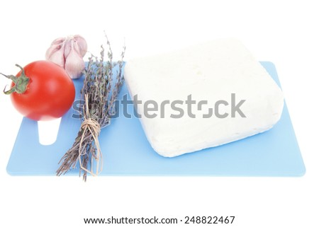 white goat cheese on cutting plate with tomato thyme and garlic isolated over white background - stock photo