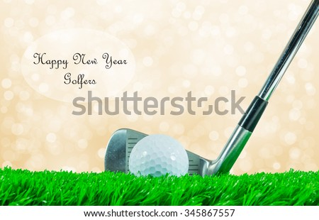 """White golf ball and iron club on green artificial grass with off focus background and quote """"Happy New Year Golfers"""" on white circle - stock photo"""