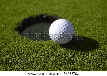White golf ball lies right at the lip of the golf hole on the green. - stock photo