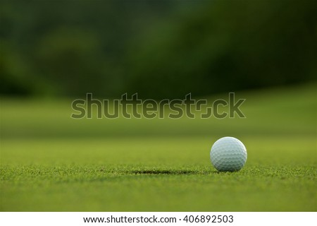 white golf ball near hole on fairway with the green background in the country side - stock photo