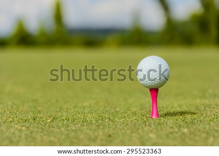 White golf ball on a pink tee - stock photo