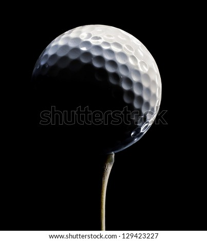 White Golf Ball on a Wooden Tee with dramatic lighting on black - stock photo