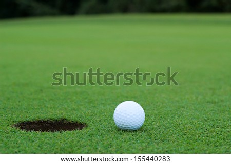 White golf ball on putting green - stock photo