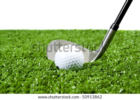 White golf ball with iron(golf club) behind it ready to hit ball on green grass (artificial turf) white background for copy space. - stock photo