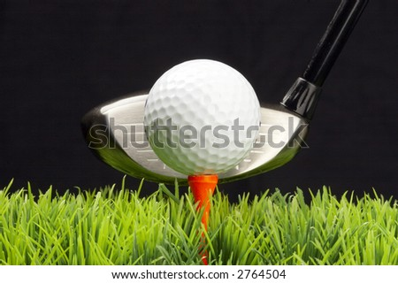 white golfball on tee, driver behind, isolated on black background - stock photo