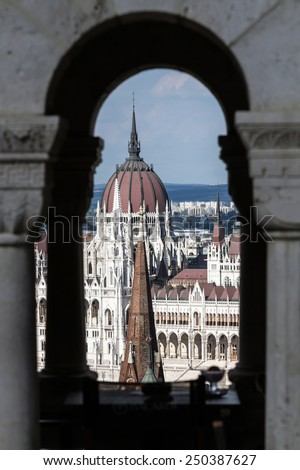 White Gothic building of the Hungarian Parliament in Budapest. The photo was taken through the window of Fisherman's Bastion - stock photo