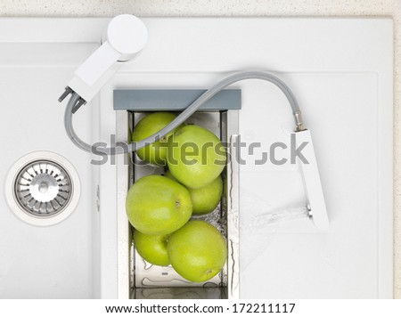 White granite kitchen sink with mixer tap, flowers and green apple. Classical interior. Water flows from the faucet with pull-watering. - stock photo