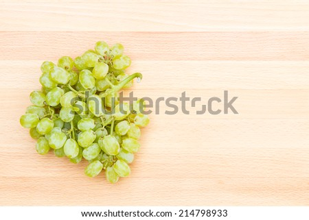 White grapes on a wooden cutting board with copyspace - stock photo