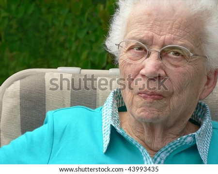 White-haired woman in lawn chair. - stock photo