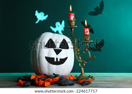White Halloween pumpkin and candles on wooden table on dark color background - stock photo