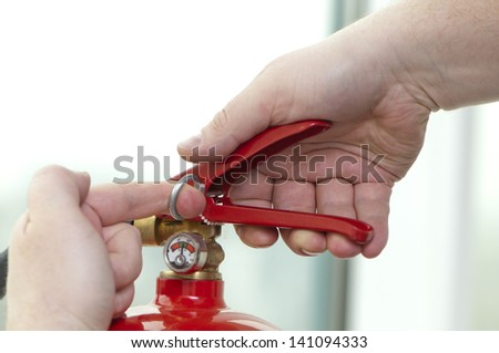 white hand presses the trigger fire extinguisher - stock photo