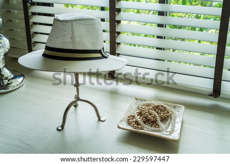 white hat and jewelry set on a dresser table in a contemporary room. - stock photo