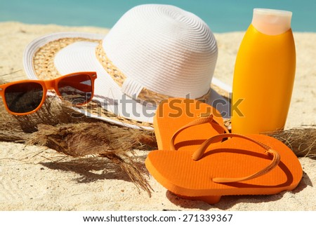 white hat flip-flops and tanning lotion on the beach - stock photo