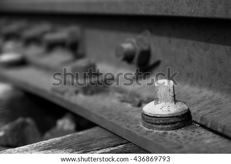 White head screw on the rusty rail track, closeup. Black and white, Industrial museum Zeche Zollern, Dortmund, Germany, 2104 - stock photo