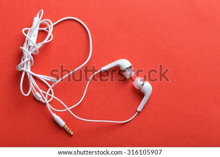 White headphones on a red paper background - stock photo