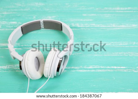 White headphones on wooden table close-up - stock photo