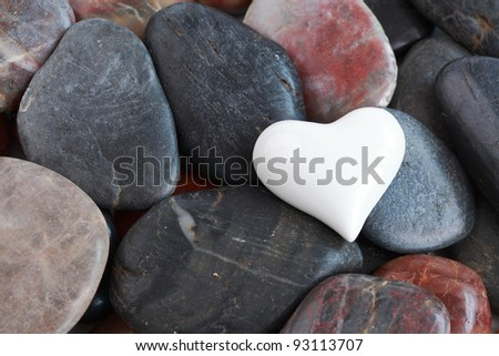 White heart heart surrounded by natural stones - stock photo
