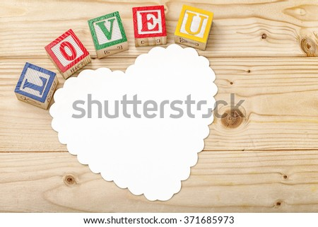 White heart shaped card on pine wood background with colorful ABC wood blocks spelling the words Love U - stock photo