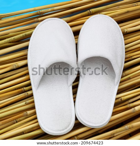 White hotel / home/ spa / wellness slippers on bamboo wood with sea - swimming pool background with space for text - stock photo
