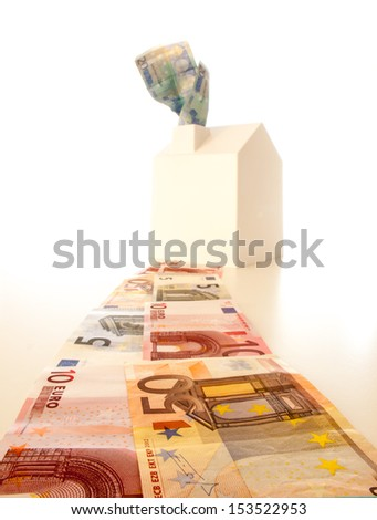 white house at the end of a path of Euro banknotes with banknotes coming out of the chimney. concept  rising cost of living. - stock photo
