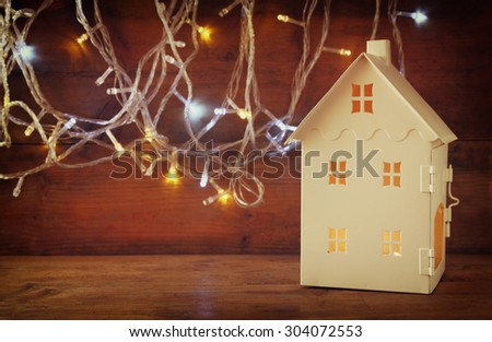 white house lantern with burning candles inside in front of garland gold lights on wooden table. retro filtered image - stock photo