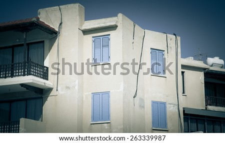 White house with blue shutters and wooden balcony. Toned. - stock photo