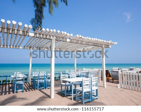 White hut with tables and chairs by the beach - stock photo