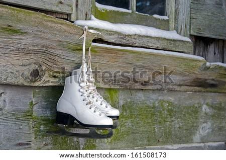 white ice skates hanging form weathered barn wood - stock photo