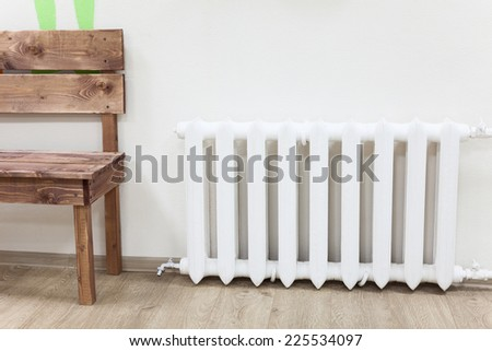 White iron radiator of central heating is near wooden bench in room - stock photo