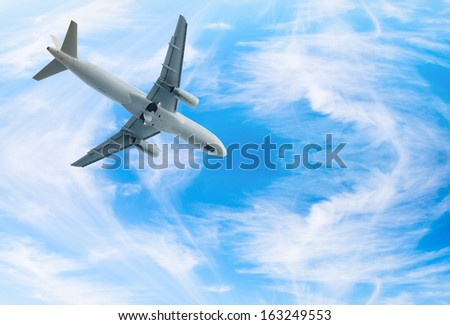 White jet airplane fly in blue bright wispy cloudy blue sky - stock photo